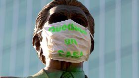 """تمثال الإيديولوجي والمعلم القانوني كونستانسيو هيرنانديز ألفيردي يرتدي قناعا للوجه كتب عليه """"البقاء في المنزل"""""""