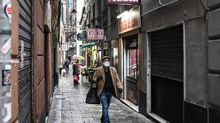 A resident wearing a protection mask carrying a shopping bag walks past shops as they close up under the lockdown in Genoa, Italy, March 13, 2020.