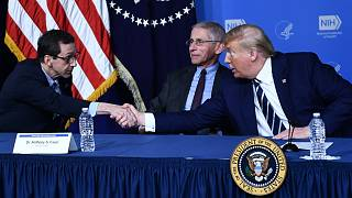 Donald Trump, amerikai elnök John Mascolának, a Vakcinakutató Központ igazgatójának a kezét rázza épp Dr. Fauci előtt
