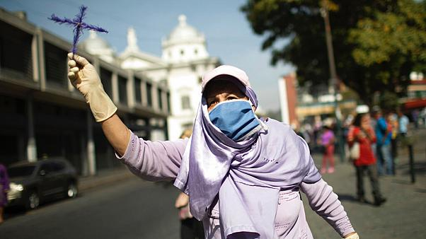 A woman holds up a cross as she tries to follow a statue of Jesus passing by during Holy Week in Caracas, Venezuela, April 8, 2020