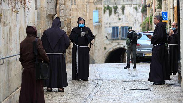 عدد من رجال الدين الفرنسيسكان بالقدس القديمة يصلون وهم يضعون أقنعة واقية من فيروس كورونا ويظهر في أقصى الصورة أفراد من الشرطة الإسرائيلية في الجمعة العظيمة.10/04/2020