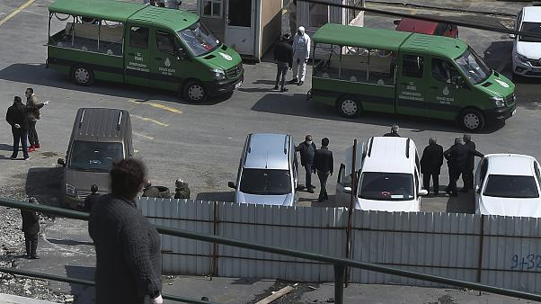People, some wearing protective face masks and suits as a preventive measure against the spread of the coronavirus wait gather around hearse trucks carrying coffins of victims