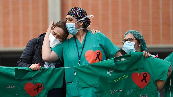 Healthcare workers (R) confort the wife of Esteban, a male nurse that died of the coronavirus
