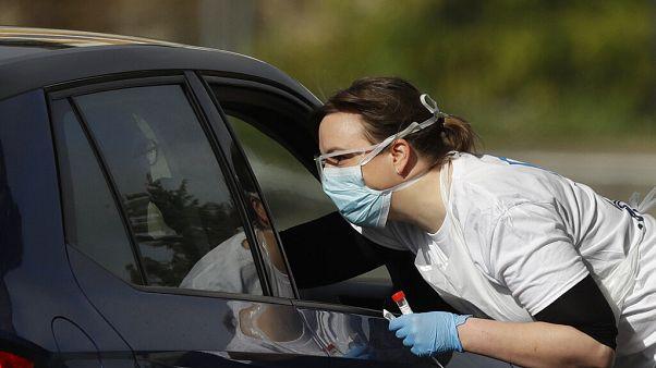 Egy egészségügyi dolgozó koronavírusteszthez vesz mintát egy autóstól