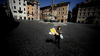 A woman carries her shopping and an Easter egg- Rome, on April 11, 2020