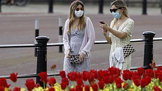 Dos mujeres pasean con máscaras protectiras cerca de Buckingham Palace