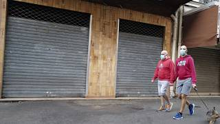 A couple wearing protective masks walks their dog front of a closed shop during a nationwide confinement to counter the COVID-19, in Paris Sunday April 12, 2020.