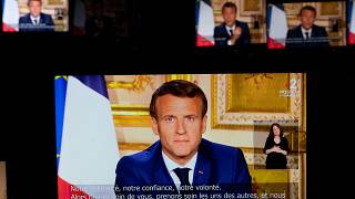 French President Emmanuel Macron is seen on multiple monitors in Paris, as he speaks from the Elysee Palace during a televised address to the nation on April 13, 2020.
