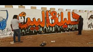 مجموعة من الشباب ينظفون شوارع العاصمة السودانية الخرطوم وجدرايات تدعو للبقاء في المنازل للوقاية من وباء كورونا