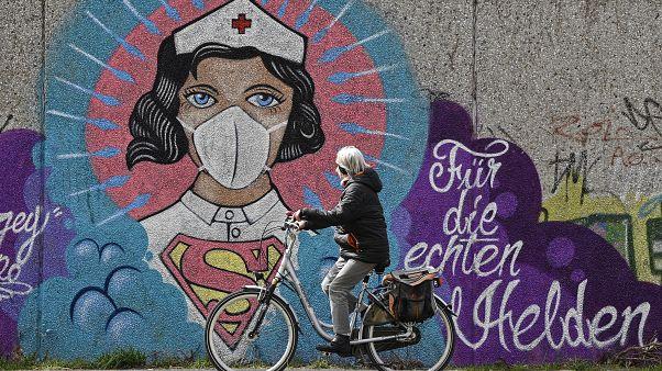 """سيدة ألمانية تسير بدراجتها بمدينة هام أمام جدارية كبيرة يظهر الممرضة كالمرأة العجيبة، وكتب عليها """"لأجل الأبطال الحقيقيين"""". 13/04/2020"""