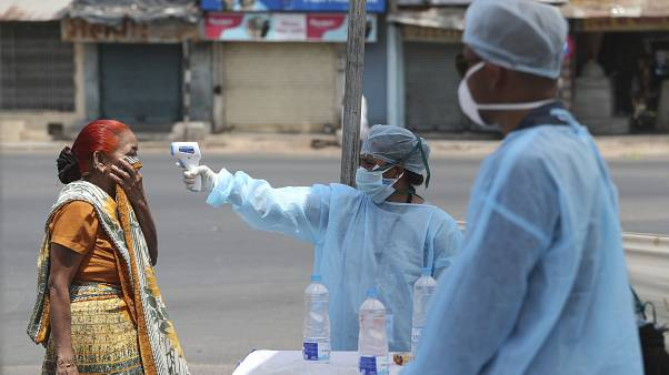 In this April 8, 2020 file photo, an Indian health worker checks the temperature of a woman during lockdown to prevent the spread of new coronavirus in Ahmedabad, India.