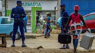 A saleswoman tries to pass the prohibited sale zone as two police officers look an at the Avo Kumbi sqaure in Luanda, Angola, on April 2, 2020.
