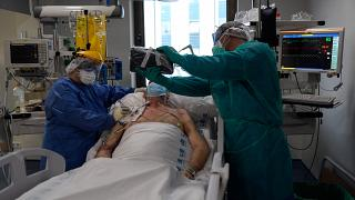 Des soignants tiennent une tablette devant un patient atteint du coronavirus COVID-19 pour qu'il appelle ses proches, à l'hôpital Ramon y Cajal de Madrid