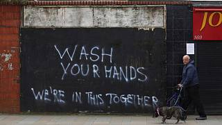 A man walks his dog past graffiti calling for people to wash their hands to combat the spread of the coronavirus, in Belfast, Northern Ireland, Monday March, 30, 2020
