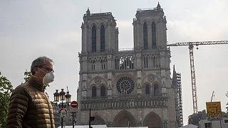 Um homem de máscara passa diante da catedral de Notre-Dame, em Paris