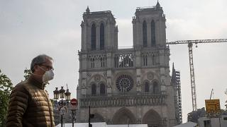 A man in a mask walks past Notre Dame Cathedral in Paris