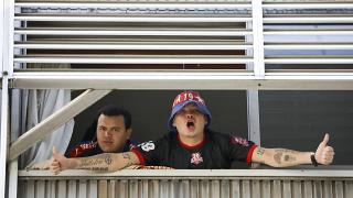 Fans of Independiente de Medellin soccer club - quarantined in Argentina - shout to journalists from a hotel in Buenos Aires, Tuesday, April 14, 2020.