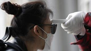 A voter has her temperature checked upon her arrival at a polling station in Seoul, South Korea, Wednesday, April 15, 2020.
