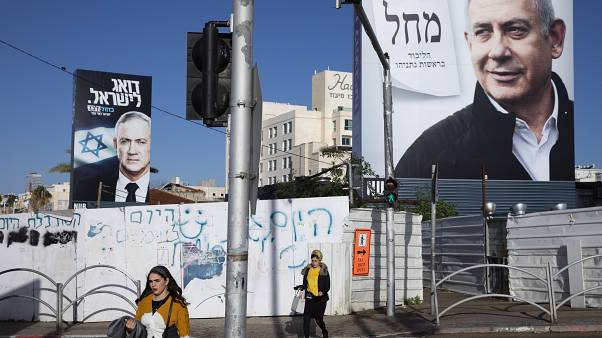 In this March. 1, 2020 file photo, people walk next to election campaign billboards showing Israeli Prime Minister Benjamin Netanyahu, right, and Benny Gantz, left, in Bnei Br