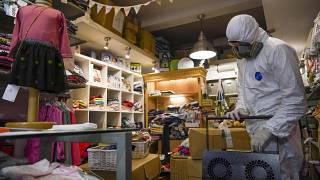 A children's clothing store is sanitised ahead of re-opening in Italy