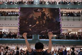 A man holds a poster in Shatin, Hong Kong, as people gather to sing 'Glory to Hong Kong', a protest song which gained popularity in the city as an unofficial anthem