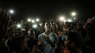 People chant slogans as a young man recites a poem, illuminated by mobile phones, before the opposition's direct dialogue with people in Khartoum on June 19, 2019