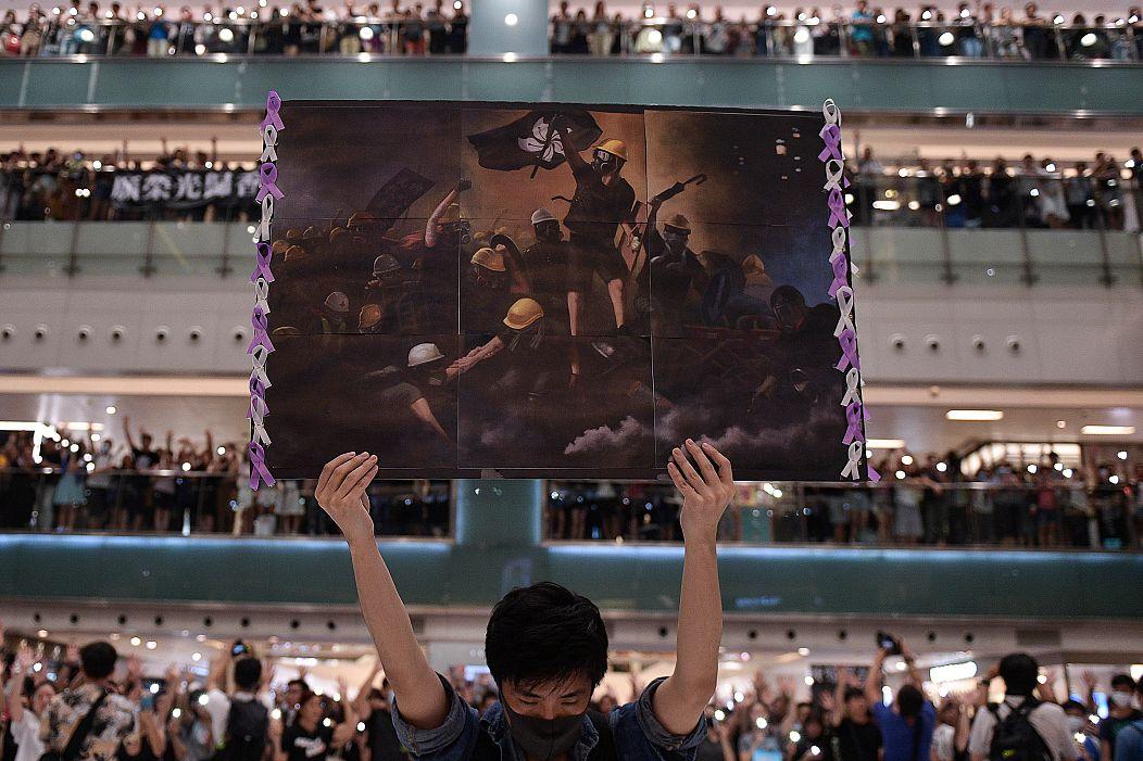 Un uomo tiene in mano un poster a Shatin, Hong Kong, mentre la gente si riunisce intorno a lui per cantare 'Glory to Hong Kong', una canzone di protesta che ha guadagnato popolarità in città come inno non ufficiale ASFOURI/AFP