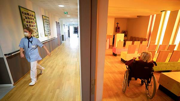 A nurse walks in a corridor of a nursing home as a resident sits in a chapel during a COVID-19 testing session in Bergheim, eastern France, Tuesday April 14, 2020