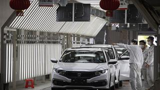In this April 8, 2020, photo, workers wearing masks against the coronavirus chat near finished cars rolled out at the Dongfeng Honda Automobile Co., Ltd factory in Wuhan.