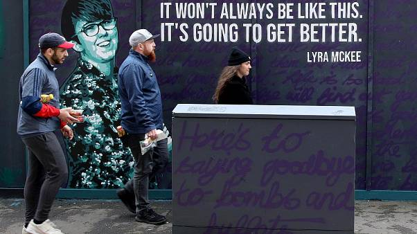 Residents walk past a newly painted mural featuring murdered journalist Lyra McKee in central Belfast on May 7, 2019