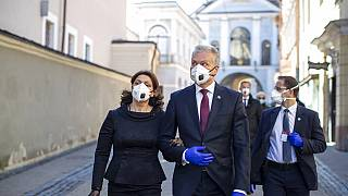 Lithuania's President Gitanas Nauseda and his wife Diana Nausediene, left, wearing face masks after leaving church in Vilnius