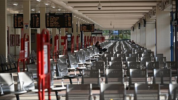 A person sits on a seat in an otherwise empty bus station in Huddersfield, northern England