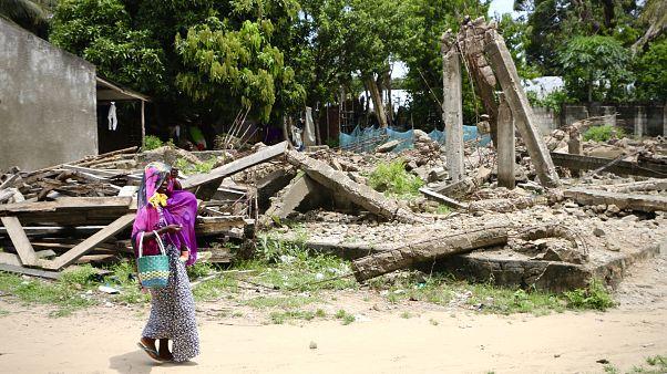 Mulher carrega criança ao colo em Moçambique