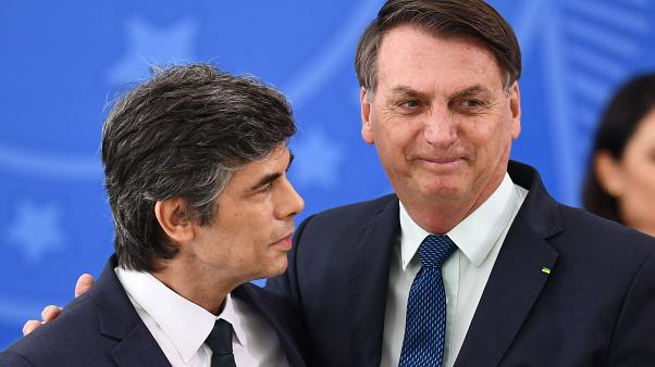 Brazilian President Jair Bolsonaro (R) embraces his new Health Minister Nelson Teich during his swearing-in ceremony at Planalto Palace in Brasilia, on April 17, 2020