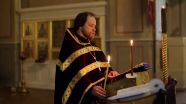 Orthodox priest conducting church service in Moscow for online worshippers