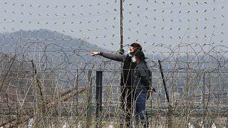 Koronavirüse karşı maske takan Güney Koreli bir çift, Kuzey Kore sınırında