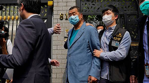 Hong Kong media tycoon Jimmy Lai, center, who founded local newspaper Apple Daily, is arrested by police officers at his home in Hong Kong, Saturday, April 18, 2020