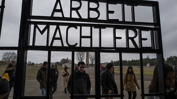 Visitors walk past the gate of the former Sachsenhausen concentration camp
