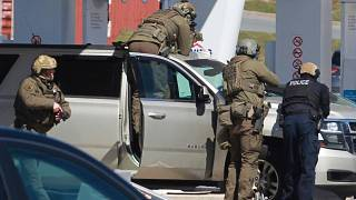 Royal Canadian Mounted Police officers surround a suspect at a gas station in Enfield, Nova Scotia, April 19, 2020