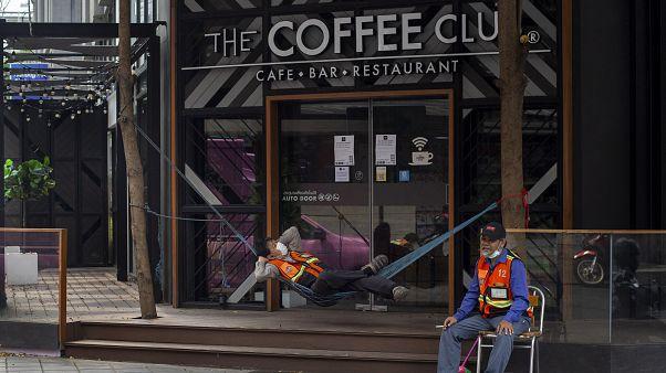 سائق دراجة نارية يأخذ قسطا من الراحة أمام مقهى مغلق بسبب الحجر الصحي المروض في بانكوك-2020/04/14