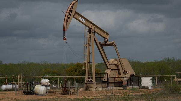 In this file photo taken on March 12, 2019 a pump jack operates at an oil extraction site in Cotulla, Texas