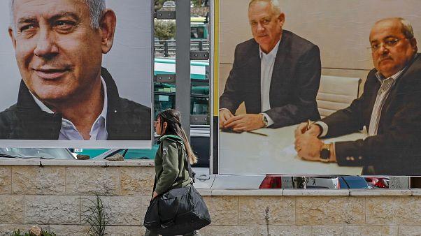 Israelische Soldatin vor Wahlplakaten mit Ministerpräsident Netanjahu und Oppositionsführer Gantz
