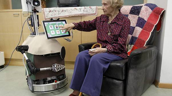 An old woman poses with care robot during a demonstration in Vienna, Austria, Thursday, March 14, 2013.