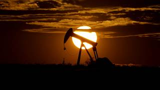 In this Wednesday, April 8, 2020, file photo, the sun sets behind an idle pump jack near Karnes City, Texas.