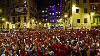 Los juerguistas sostienen velas y pañuelos rojos cantando ''Pobre de Mi'' para cerrar San Fermín 2019 el 15 de julio en Pamplona.