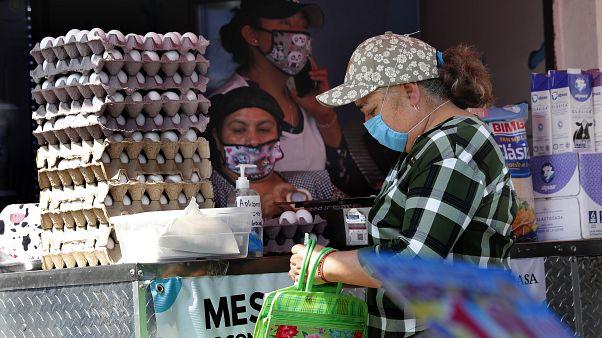 Una mujer compra en un mercado mexicano