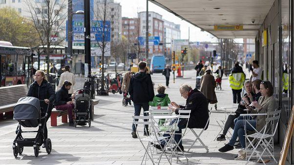 Des gens mangent des glaces dans un café en plein air alors que d'autres passent dans le centre de Stockholm, en Suède, le lundi 20 avril 2020.