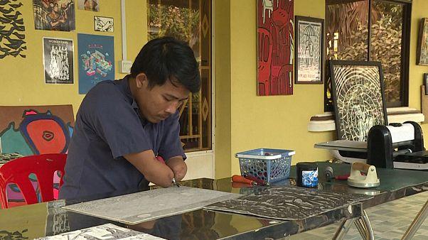 هنرمند معلول کامبوجی رنجهای جامعه را نقش میزند