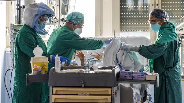 Medical workers tend to a patient at the Intensive Care Unit of the Tor Vergata Covid-4 hospital on April 21, 2020 in Rome