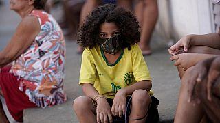 Uma criança protege-se da Covid-19 na favela Mandela, Rio de Janeiro